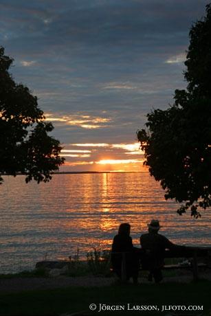 Par på parkbänk i solnedgången