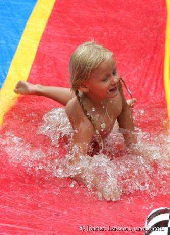 Barn som leker i vattenrutschbana