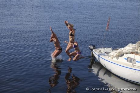 Flickor  badar från segelbåt, Misterhults skärgård