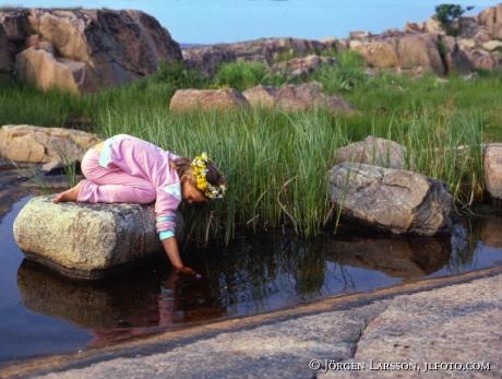 Flicka med blomsterkrans på sten med